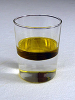 An image of a thick layer of oil floating on water in an ordinary glass